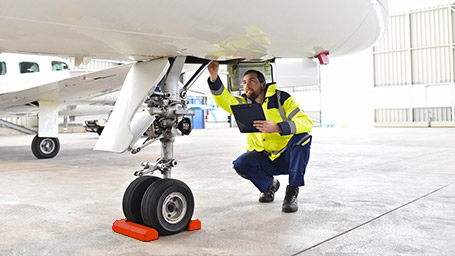 Airplane mechanic inspects wheel of plane